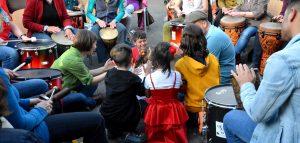 Peter Kaiser und Helga Reihl knien mit 5 Kindern in der Mitte eines Kreises und klatschen mit den Kindern. Die Erwachsenen im äußeren Kreis trommeln.