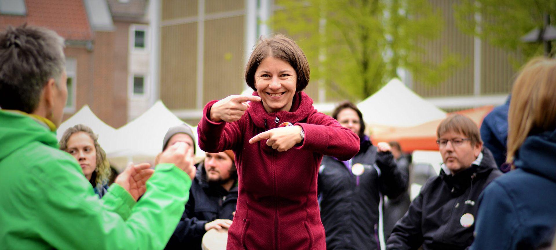 Helga Reihl beim Drum Circle auf dem Marktplatz in Lübeck. Mit einer Geste lädt sie zum Weiterspielen ein.