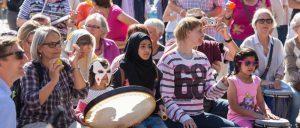 Über 100 Menschen auf dem Marktplatz in Mölln trommeln gemeinsam mit Helga Reihl und Peter Kaiser