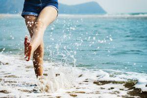 Eine Frau läuft barfuss am Strand und spritzt mit den Füßen Wasser hoch