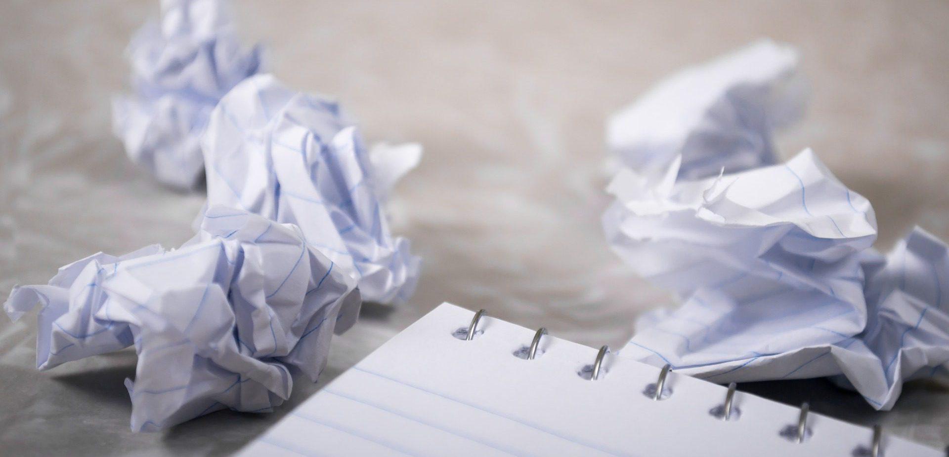 Ein Schreibblock mit einigen herausgerissenen und zerknüllten Seiten.